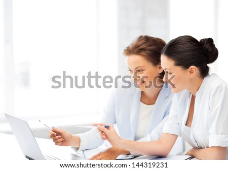 two smiling businesswomen working with laptop in office - stock photo
