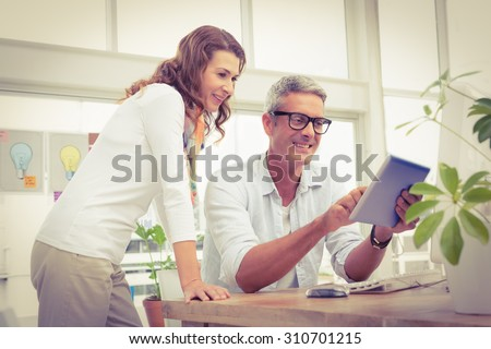 Two smiling casual designers working with tablet in the office - stock photo