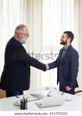 Two smiling caucasian business partners handshaking