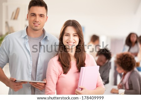 Two smiling Caucasian college students standing in front of their peers.