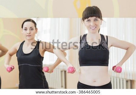 Two Smiling Caucasian Sports Women Exercising With Barbells Indoors. Horizontal Shot - stock photo