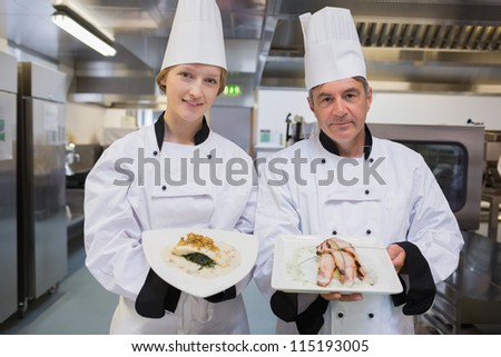 Two smiling Chef's showing their dishes in kitchen - stock photo