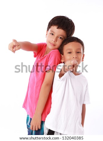 Two smiling children are pointing a distant object