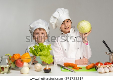 two smiling children-cooks by the table with vegetables in hands