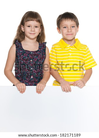 Two smiling children hold a white sheet of paper - stock photo