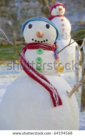 Two smiling Christmas snowmen, with colorfull scarfs and barrets - stock photo