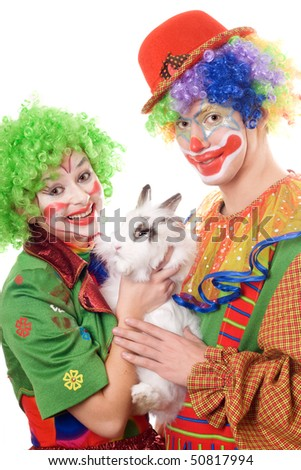 Two smiling clown with a white rabbit - stock photo