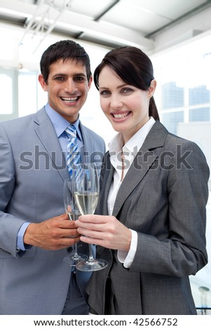Two smiling colleagues drinking Champagne to celebrate a success