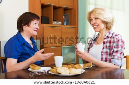 Two smiling colleagues in years drinking tea and talking during pause for lunch - stock photo