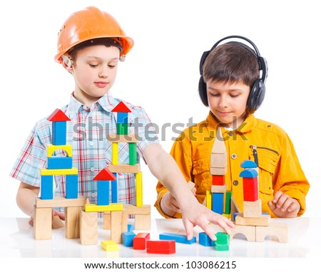 Two smiling cute boys is building a toy block. Isolated on white background - stock photo