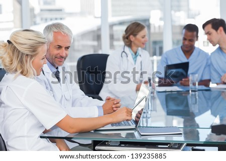 Two smiling doctors using laptop in front of medical team - stock photo