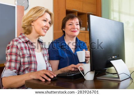 Two smiling elderly female sitting in front of PC with tea and laughing - stock photo