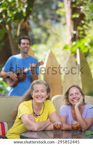 Two smiling female friends near ukulele player in Hawaii - stock photo