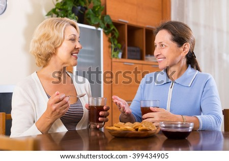 Two smiling female pensioners drinking tea indoor. Focus on blonde