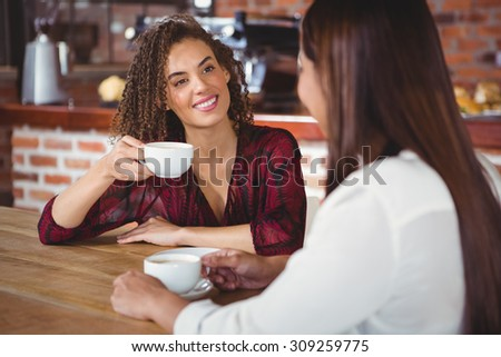 Two smiling friends having coffee at coffee shop