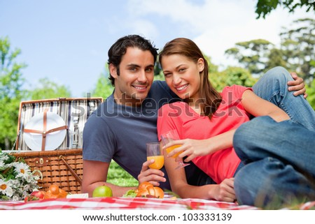 Two smiling friends looking directly in front of them while they hold glasses as they lie on a blanket with a view of the sky in the background - stock photo