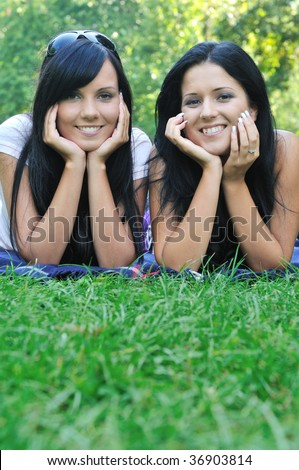 Two smiling friends lying together in grass outdoors with copy space - stock photo