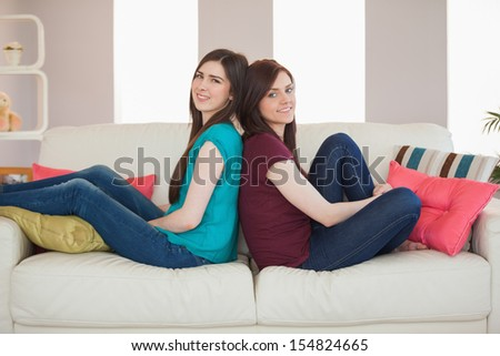 Two smiling friends sitting back to back on the sofa at home in living room
