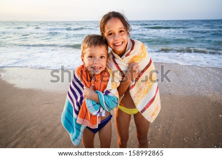 Two smiling frozen kids on the beach, outdoor - stock photo