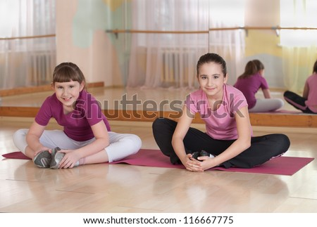 Two smiling girls engaged in physical training in the gym. Horizontal.