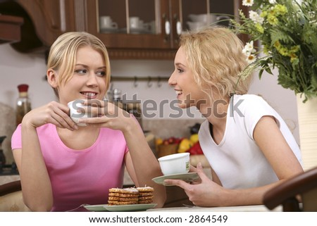 Two smiling girls have tea with tasty cookies in the kitchen - stock photo