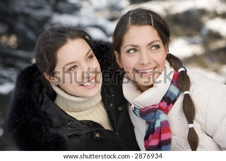 Two smiling girls having fun in the winter forest - stock photo