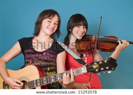 Two smiling girls holding string instruments as if ready to entertain you. - stock photo