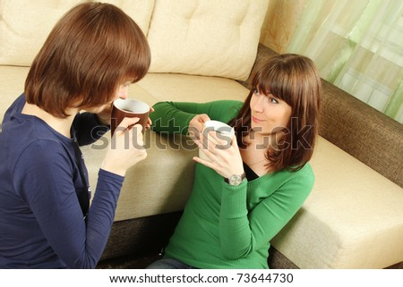 Two smiling girls in the room drinking tea, chatting and playing - stock photo