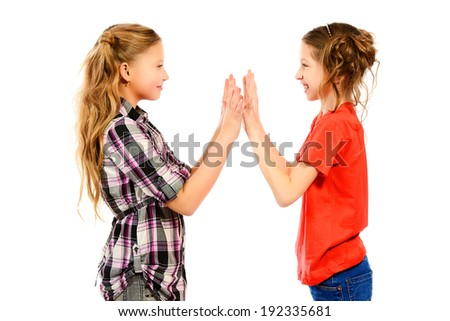 Two smiling girls standing together and playing. Isolated over white. - stock photo