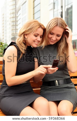 Two smiling girls watching something in mobile phone - stock photo