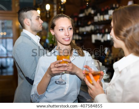 Two smiling girls with man chatting at bar of restaurant. Focus on girl - stock photo