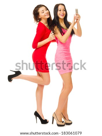 Two smiling girls with mobile phone isolated - stock photo