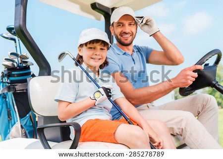 Two smiling golfers. Happy young man and his little son sitting in golf cart and looking at camera - stock photo