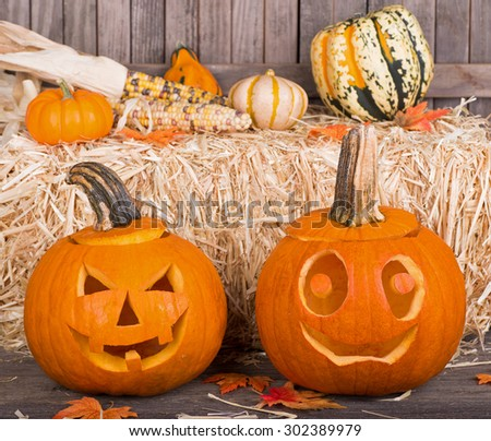 Two smiling halloween pumpkins with straw bale in background - stock photo