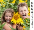 Two smiling happy children in sunflowers field shows their tongues - stock photo