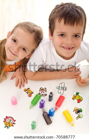Two smiling happy kids painting with lots of colors in small bottles - top view - stock photo