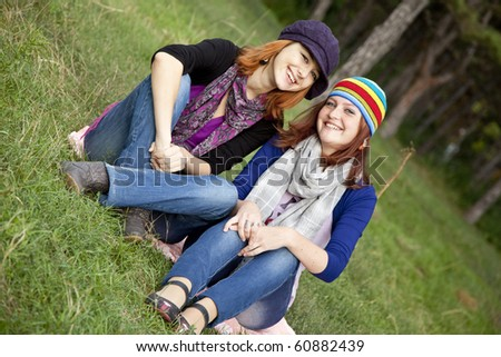 Two smiling happy sisters sitting together in grass outdoors