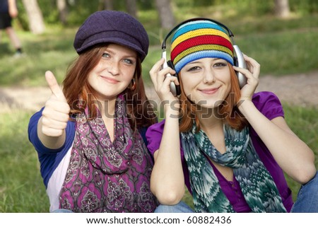 Two smiling happy sisters together in grass outdoors. One with headphones.