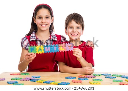 Two smiling kids at the table with puzzle letters showing family, isolated on white