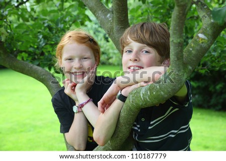 Two smiling kids in the garden - stock photo