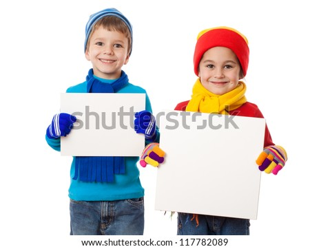 Two smiling kids in winter clothes standing with empty blank in hands, isolated on white - stock photo