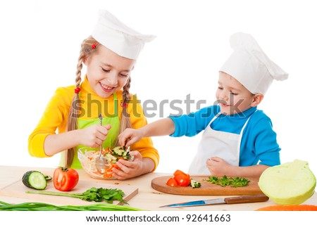 Two smiling kids mixing salad, isolated on white - stock photo