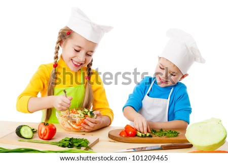 Two smiling kids mixing vegetable salad, isolated on white - stock photo