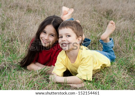 Two smiling kids on the autumn grass, outdoor - stock photo