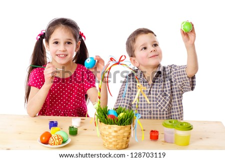 Two smiling kids paint easter eggs, isolated on white - stock photo