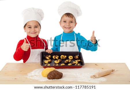 Two smiling kids with baking and thumbs up sign, isolated on white - stock photo