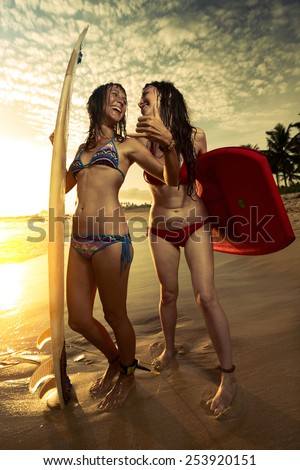 Two smiling ladies surfers standing with surf boards on the beach and showing shaka signs - stock photo