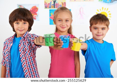 Two smiling little boys and cute girl looking at camera and holding colorful cans with paint. Preschool center for children - stock photo