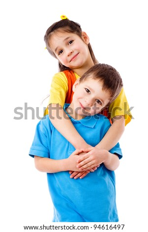 Two smiling little children standing together, isolated on white