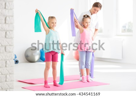 Two smiling little girls having a physical therapy session with a female PT - stock photo